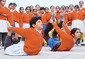 Girls of this saffron outfit school doing saffron yoga in saffron outfit.