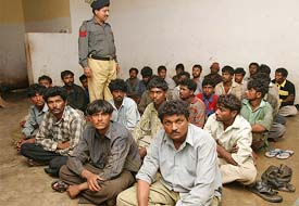 Detained Indian fishermen sit inside a police station in Karachi