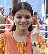 Small screen actress and BJP supporter Prachi Shah shows her marked finger after casting her vote