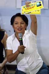 Philippine President Gloria Macapagal Arroyo promotes a car-less day sticker for motorists as she campaigns for energy conservation among the public and government officials in Manila on Saturday