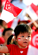 A cute small girl holding singapore's flag