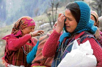 Women mourn the loss after the devastating fire in Malana on Saturday.