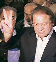 Former prime minister Nawaz Sharif holds up his ballot paper and flashes the victory sign at a polling station in Lahore