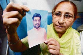 In this file picture Dalbir Kaur shows the photo of her brother Sarabjit Singh