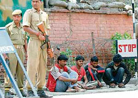 CRPF jawans stand guard over labourers held for questioning following a grenade attack in Srinagar on Saturday.