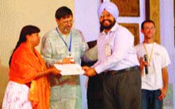 Anantdeep Singh being presented a scroll of honour by Charles Gibbs, executive director, URI, and Yoland Trevino, chairperson, Global Council, URI.