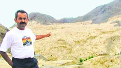 Ritesh Arya with lamayuru deposits in Ladakh, once a glacier, in the background.