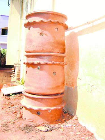 The quaint three-tiered urn-like terracotta object is called 'kambha', a compost bin for organic garbage
