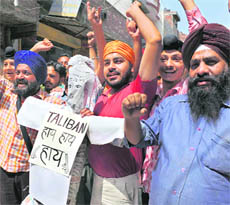 Members of the Youth Akali Dal shout slogans as they hold an effigy of Taliban during a demonstration in Amritsar on Thursday.