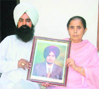 Maninderpal Singh's parents with his photograph.  Maninderpal died under mysterious circumstances in Australia last year.