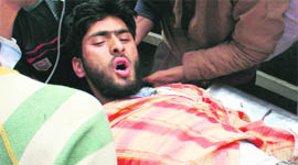 An injured being carried to a hospital in Srinagar on Monday.