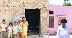 Tarsem Singh, a landless labourer of Melak Kangan village in Moga district, along with his family, outside his house. His name has not been included in the BPL list; (right) Sarpanch Sukhdev Singh, who has a four-room pucca house, has his name included in the list of beneficiaries of the Indira Awaas Yojna.