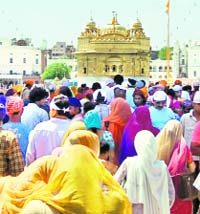 Devotees enter the Golden Temple to pay obeisance on the occasion of Amavasya in Amritsar on Monday.