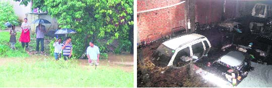 Residents cross a flooded stream at Nehru Gram and (right) submerged cars in a workshop in Dehradun on Saturday.