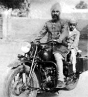 Jagjit Singh straddled across a Bullet motorcycle behind his father