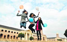 Three girls enjoy the last day of 2011 at the Forest Research Institute in Dehradun on Saturday