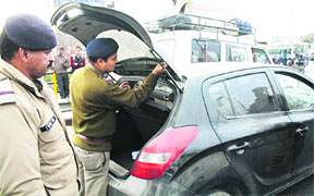 Policemen check vehicles for liquor and removing tinted strips from a car in Dehradun on Thursday.