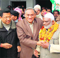 Hussain Ahmed, senior Samajwadi Party leader, being greeted by Vijay Bahuguna, Congress MP from Tehri, in Dehradun on Wednesday.