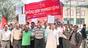 Members of the District Dehradun Driver Conductor Union hold a protest in Dehradun