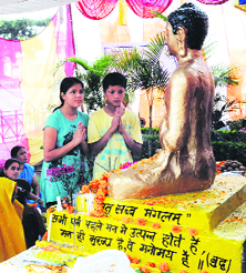 People pay obeisance at the statue of Lord Buddha on the occasion of Buddha Purnima in Dehradun on Sunday