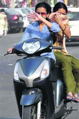 Two girls cover their faces to save themselves from dusty winds that hit Haridwar city.