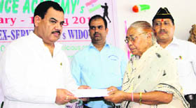 Agriculture and Sainik Welfare Minister Harak Singh Rawat gives a cheque to a widow at a function organised by the Doon Defence Academy in Dehradun on Tuesday.