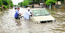 A man pushes his car in a waterlogged road at Power House Road in Bathinda on Friday